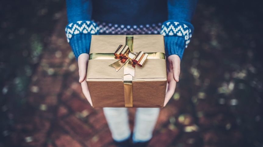 Teen girl holds a gift in her hands.