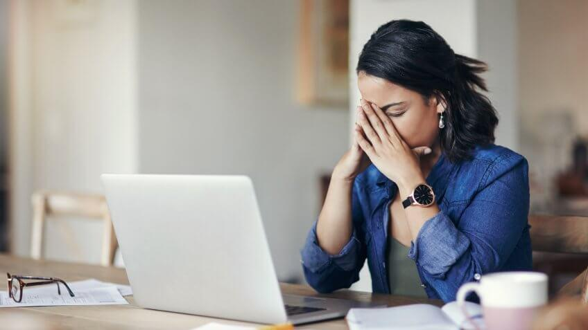 Shot of a young woman looking stressed while using a laptop to work from home.