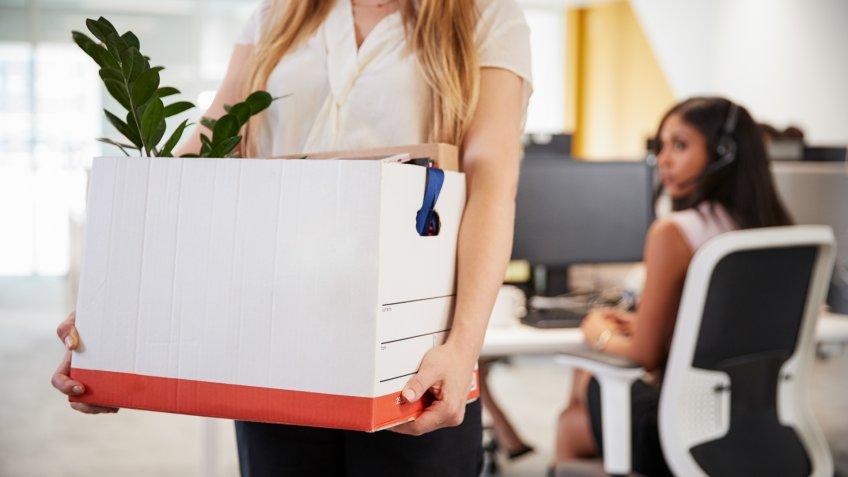 Fired female employee holding box of belongings in an office.