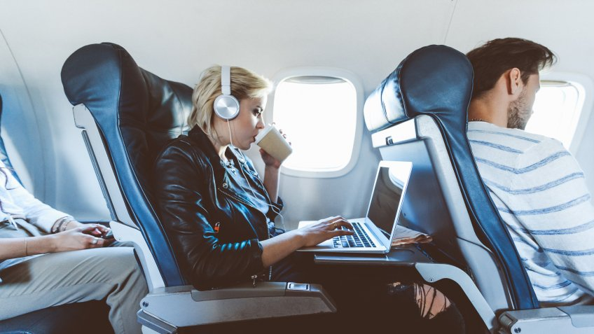 Young blonde woman sitting inside an airplane, using laptop and drinking coffee.