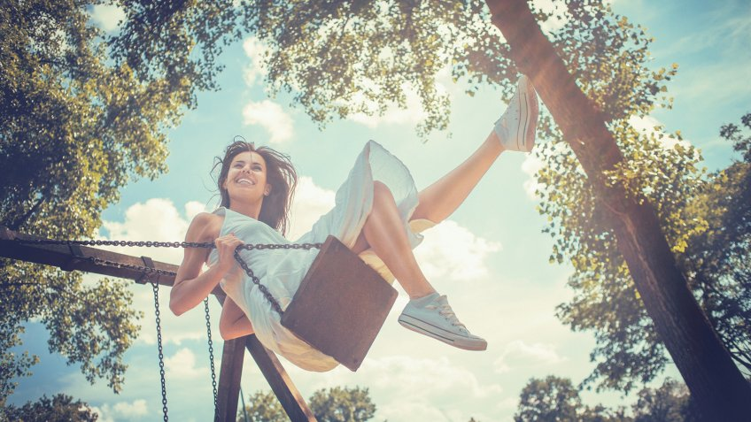 A happy young woman laughing on a bright sunny day while having fun on a swing in the park.