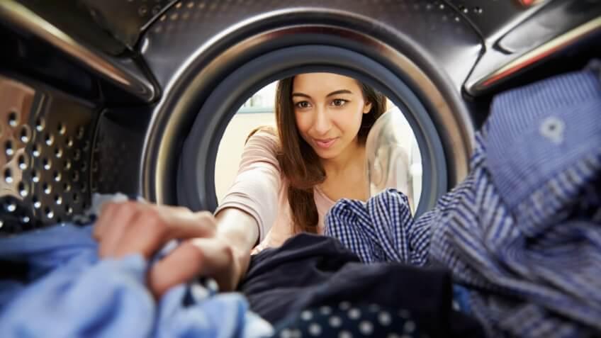 Woman Doing Laundry Reaching Inside Washing Machine.
