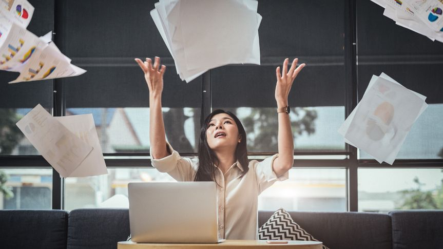 woman throwing up paper resigning from work