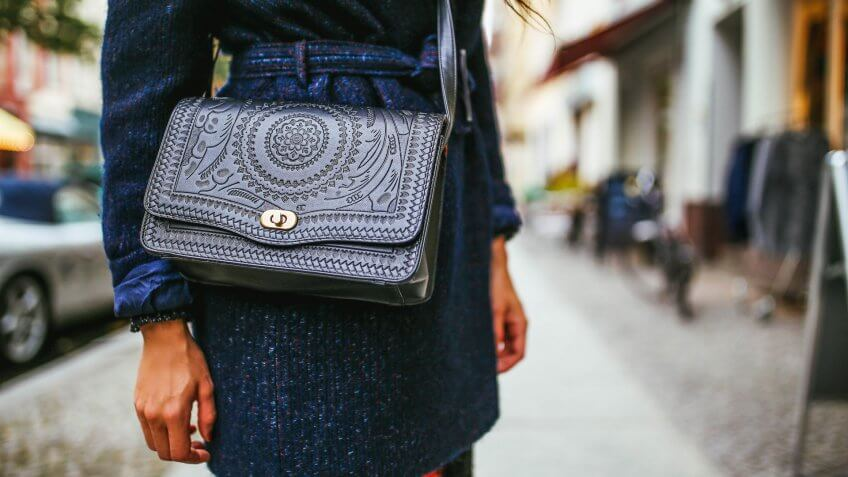 Close up on the young woman's purse and a dark coat on the streets of Berlin, in Kreuzberg - Schoneberg district.