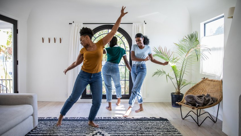 Women friends having fun at home dancing and singing in the living room of their Los Angeles apartment.