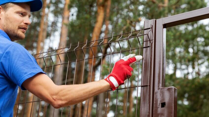 territory enclosure - worker installing metal fence.