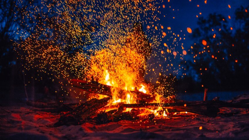 Summer beach bonfire with sparks flying around and flames blazing.