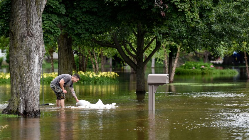 Mandatory Credit: Photo by AP/Shutterstock (8961619a)A man picks up sandbags to reinforce the barrier he build to keep the flood water from reaching his house, in Gurnee, Ill.