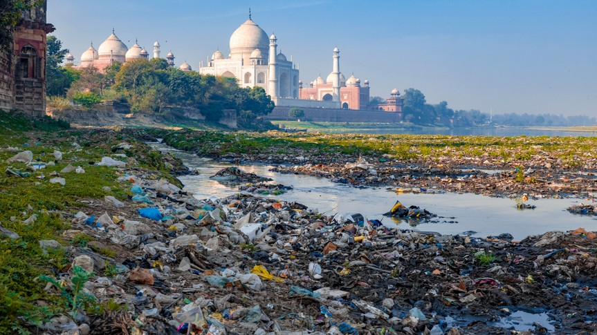 Indias contrast of ugly pollution and stunning beauty, The banks of Yamuna River polluted with garbage and beautiful Taj Mahal in the background - Image.