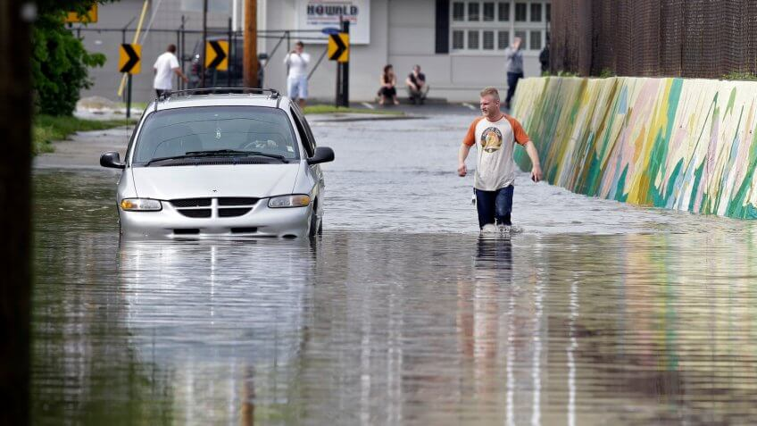Mandatory Credit: Photo by Michael Conroy/AP/Shutterstock (6244417a)A pedestrian walks past a stranded vehicle caught in rising flood waters after heavy rain fell in IndianapolisIndiana Storms, Indianapolis, USA.