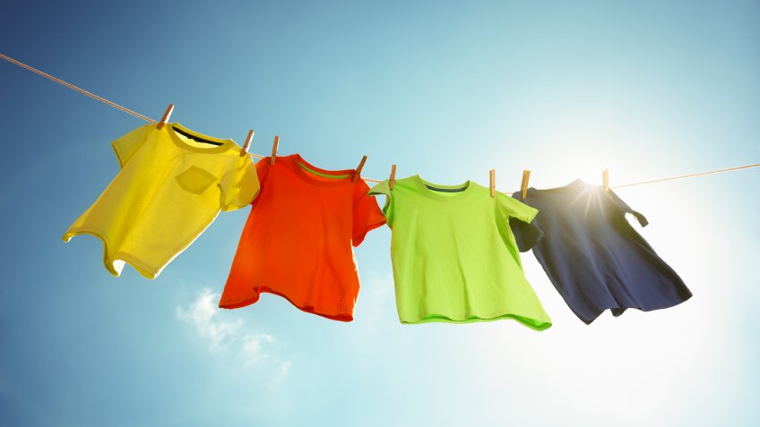 T-shirts hanging on a clothesline in front of blue sky and sun.