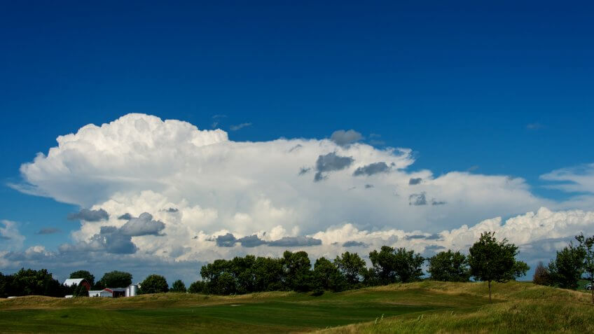 Gathering storm clouds over a tree line and distant farm buildings, Ankeny, Iowa - Image.