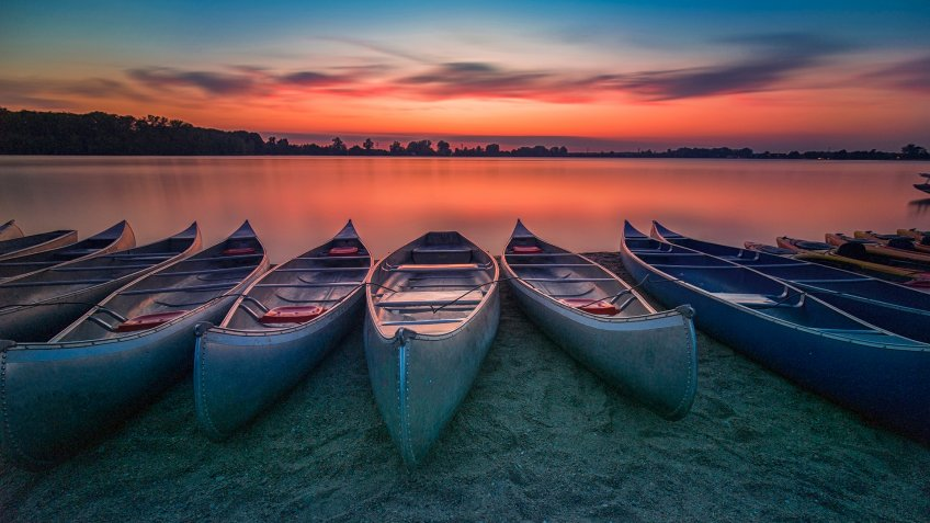 Long exposure picture of Sunset over Creve Couer lake with boats in foreground in Creve Couer, Missouri, USA - Image.