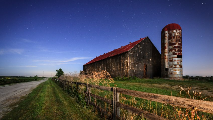 Scenic nighttime image of an old farm barn and a country road in moonlight.