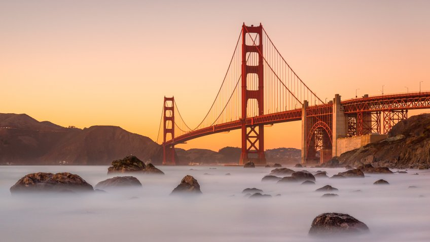 Long exposure photo in Marshall's Beach with Golden Gate Bridge in the background in San Francisco at sunset, California.