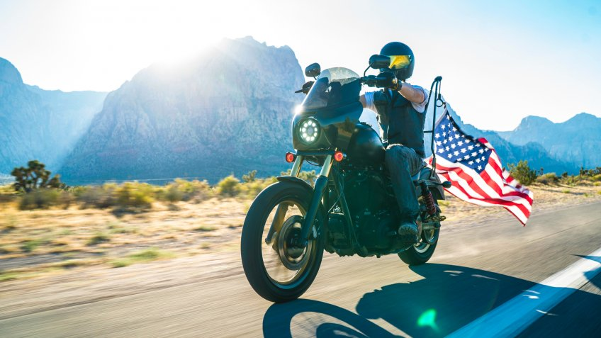 Harley Davidson motorcycle with American flag on the road