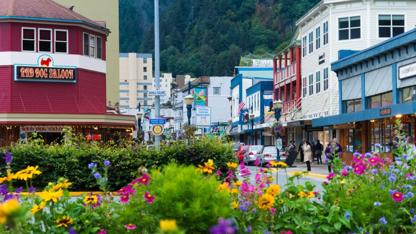 Alaska, USA - August 12, 2016: Downtown Juneau with flowers in the foreground with painted wooden storefront buildings and the Red Dog Saloon.