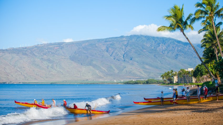 Maui, Hawaii, USA - March 15, 2012: People paddle outrigger canoes off the beach at sunrise.