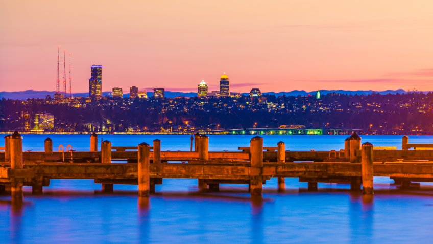 dock with background of Bellevue cityscape with reflection on lake washington at night.
