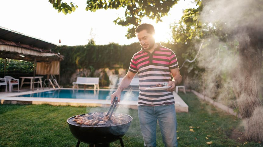 A mid adult man is cooking meat on bbq.