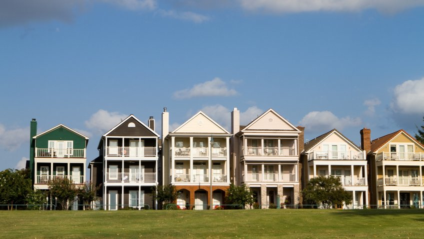 Upscale townhomes for the wealthy built on a grass hill in a row against a cloudy blue sky in Memphis, Tennessee.