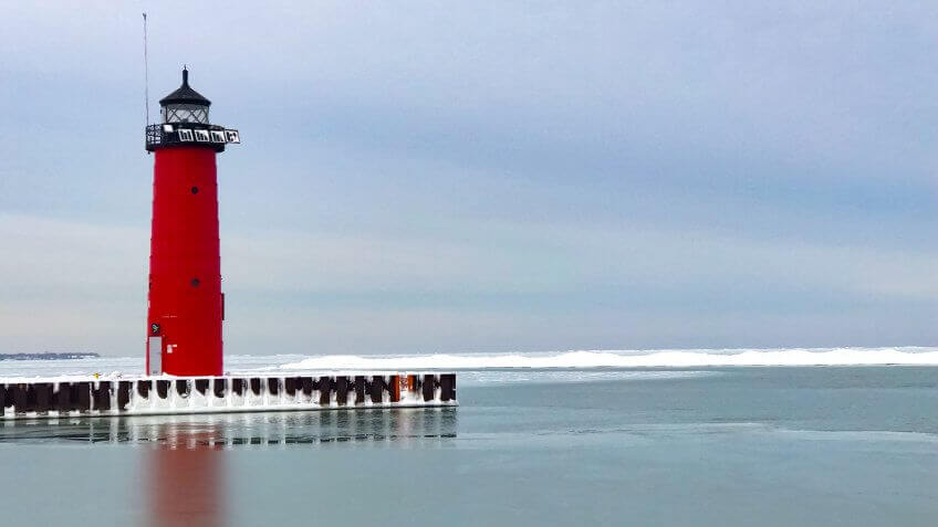 Red lighthouse at Michigan Lake in Kenosha, Wisconsin, USA on blue cloud sky in winter.