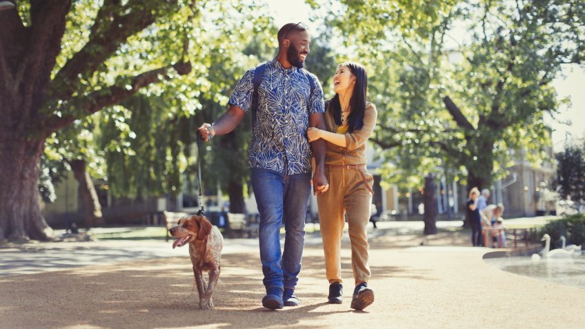 Happy young couple walking dog in sunny park.