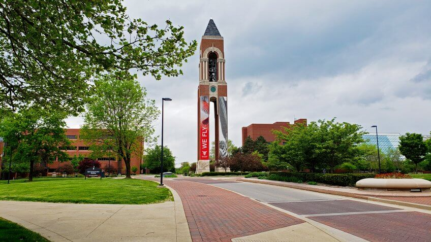 Muncie, Indiana / United States - May10, 2019 Ball State University Shafer Bell Tower with road, sidewalk, trees and overcast sky in springtime.