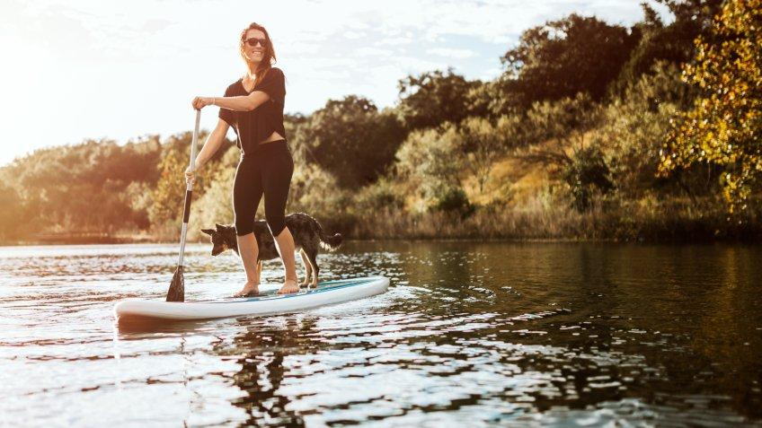 A beautiful young adult woman enjoys a peaceful moment on the water with her paddle board and faithful pet dog.
