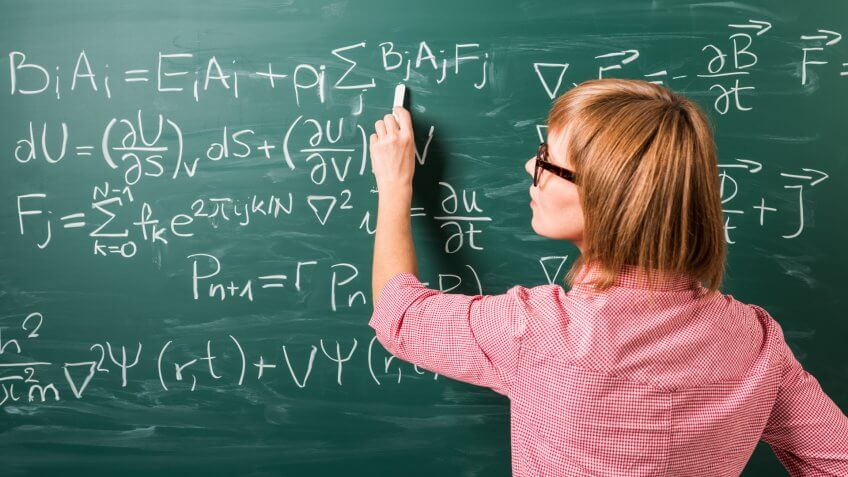 """Close-up on woman in glasses standing against green chalkboard."