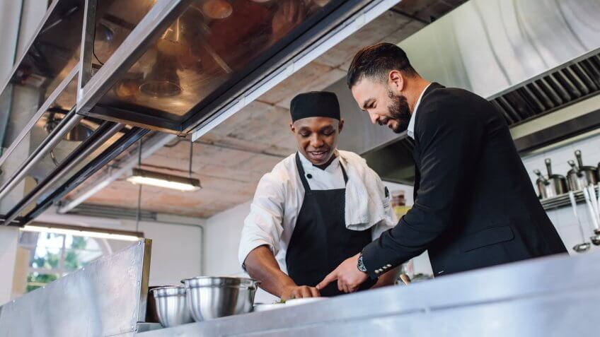 Restaurant manager discussing with chef in kitchen.