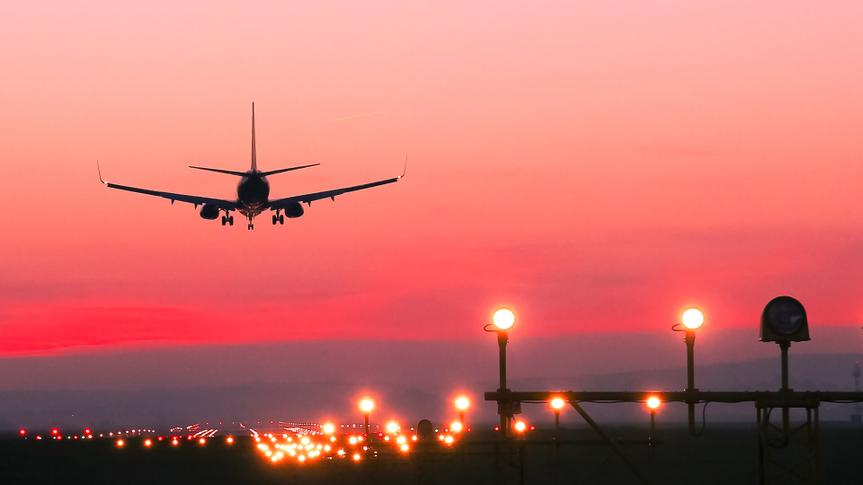 Plane lands at an airfield at the sunset.