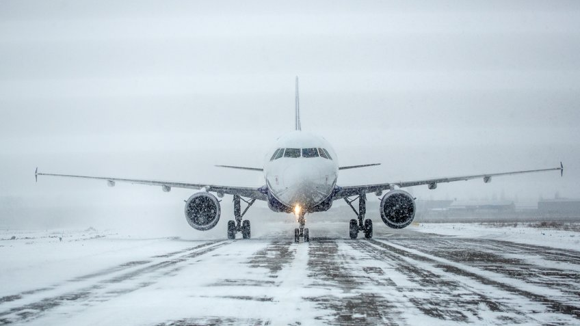 Airliner on runway in blizzard.