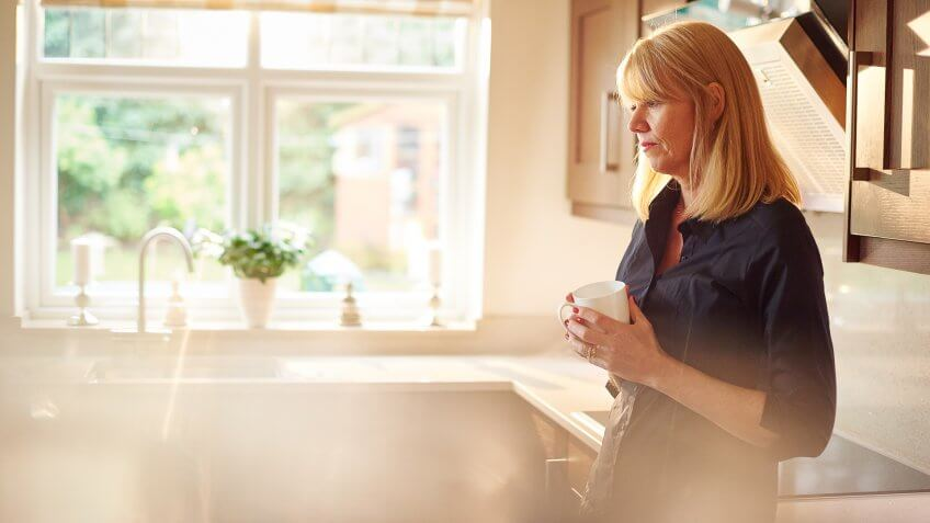 a woman stands in her kitchen and has a cuppa and a break looking to the floor in sad contemplation.