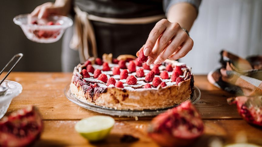 Woman Putting Raspberries To American Blackberry Pie, While It Is In  Mold.