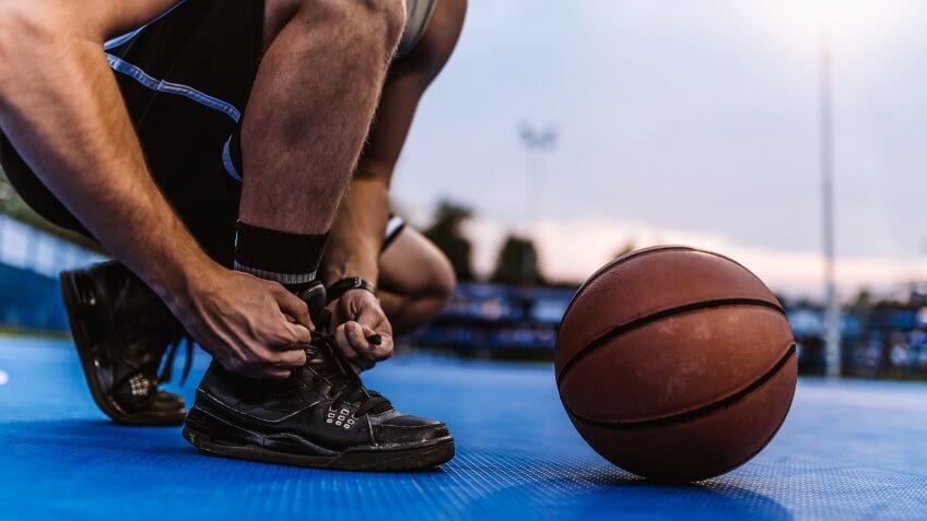 Photo of Unrecognizable Person, Basketball male Caucasian young player tying sport shoes in the summer evening with a basketball by his side.