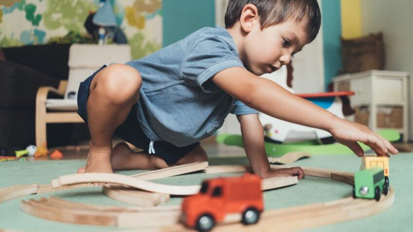 Cute little boy playing with wooden train on the floor at home.