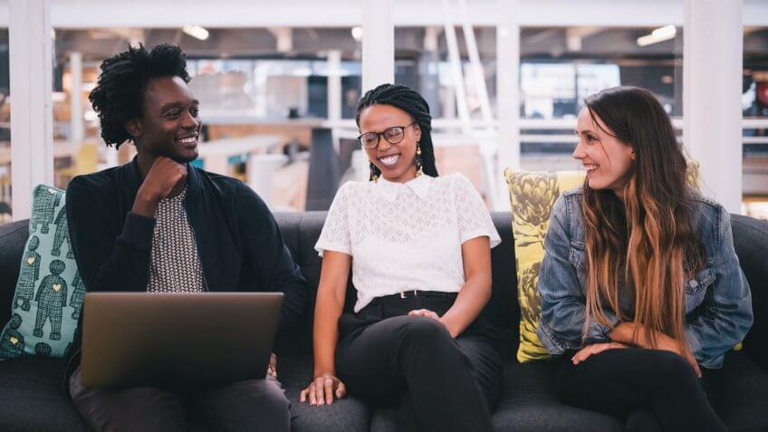 employees smiling while holding discussion on tech startup office couch