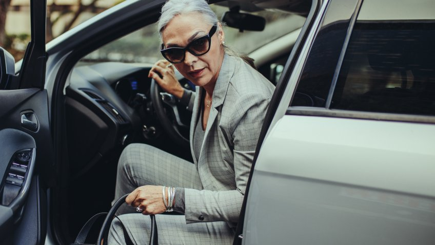 Senior businesswoman with purse getting out of her car.