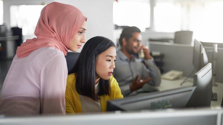 Businesswomen discussing over desktop PC in office.