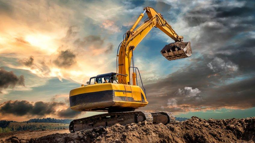 Crawler excavator during earthmoving works on construction site at dawn.