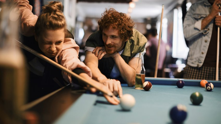 Close up of a group of friend playing pool.