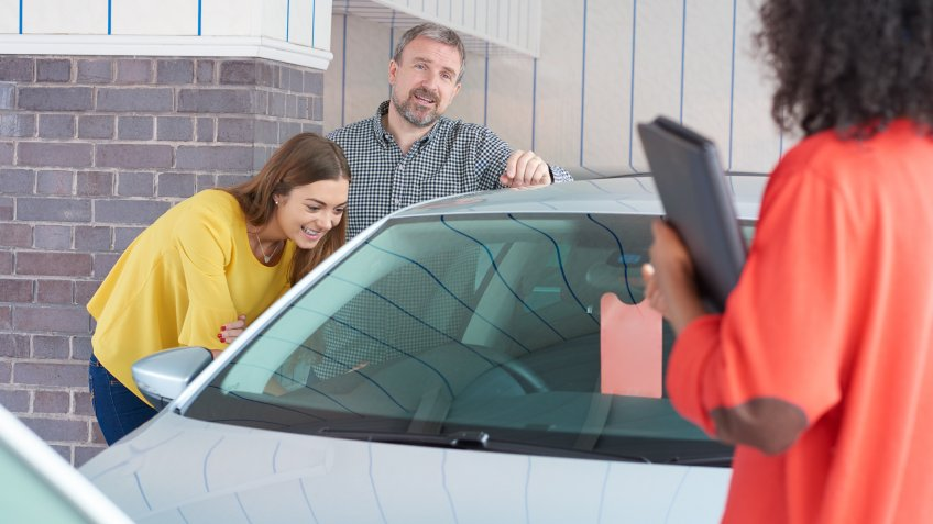 A mature man and his young daughter are looking at  cars in a car showrooms .