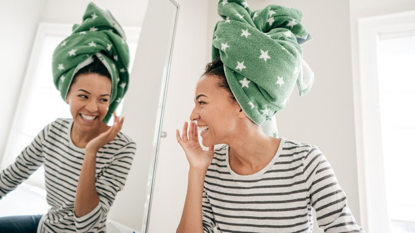 Woman with towel smiling to mirror.