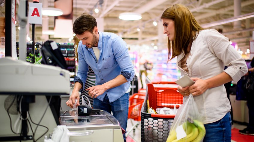 Heterosexual couple in the supermarket packing groceries on the checkout.