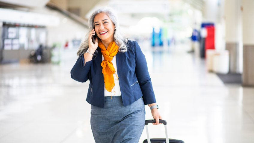 A Senior Hispanic Woman using her phone in the airport.