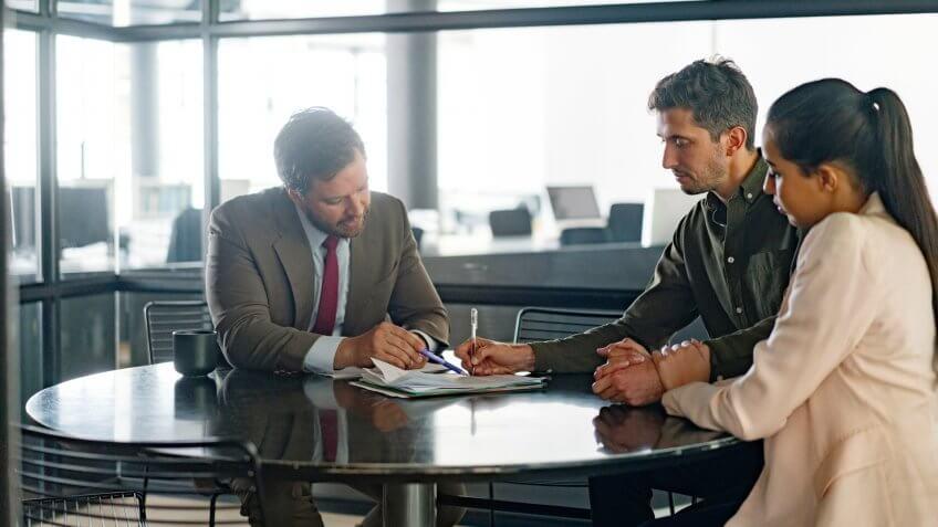 Confident financial advisor explaining agreement to customers.
