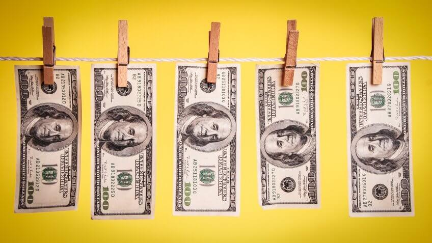 500 dollars hanging on a clothesline against a yellow background.