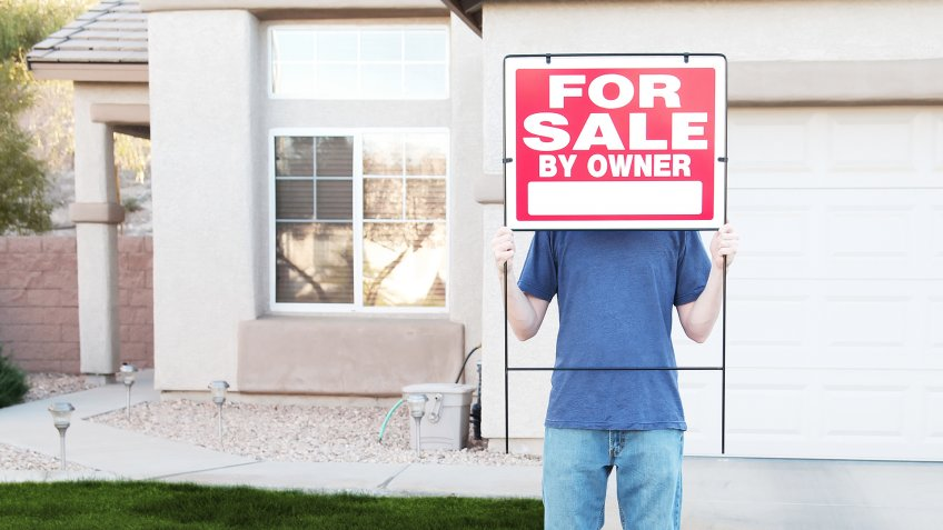 """Photo of a man standing in front of his house, hiding behind a For Sale sign."