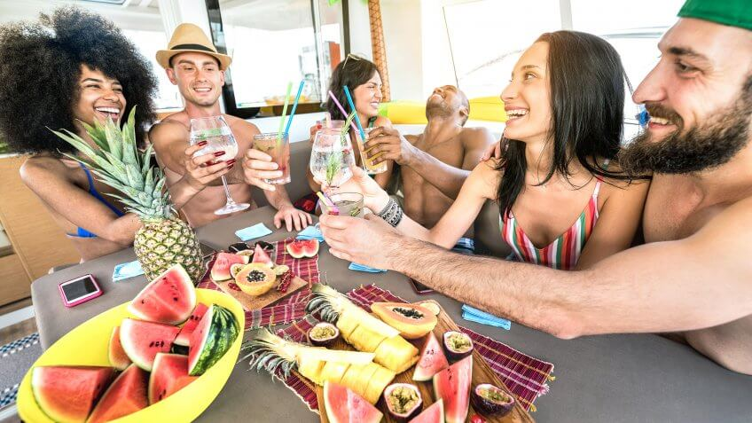 Happy friends drinking fancy cocktails at boat party trip - Young millenial people having fun on luxury vacation - Travel lifestyle concept with millennials sharing aperitif drinks with tropical fruit - Image.